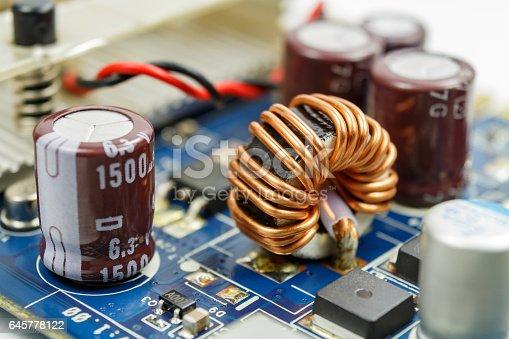 istock Transformer on a ferrite ring on the circuit board closeup 645778122