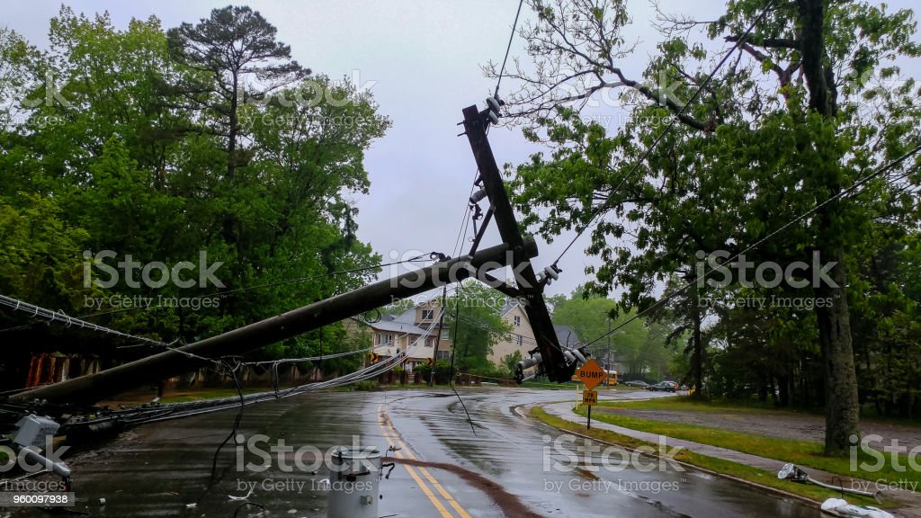 transformer on a pole and a tree laying across power lines over a road after Hurricane moved across royalty-free stock photo