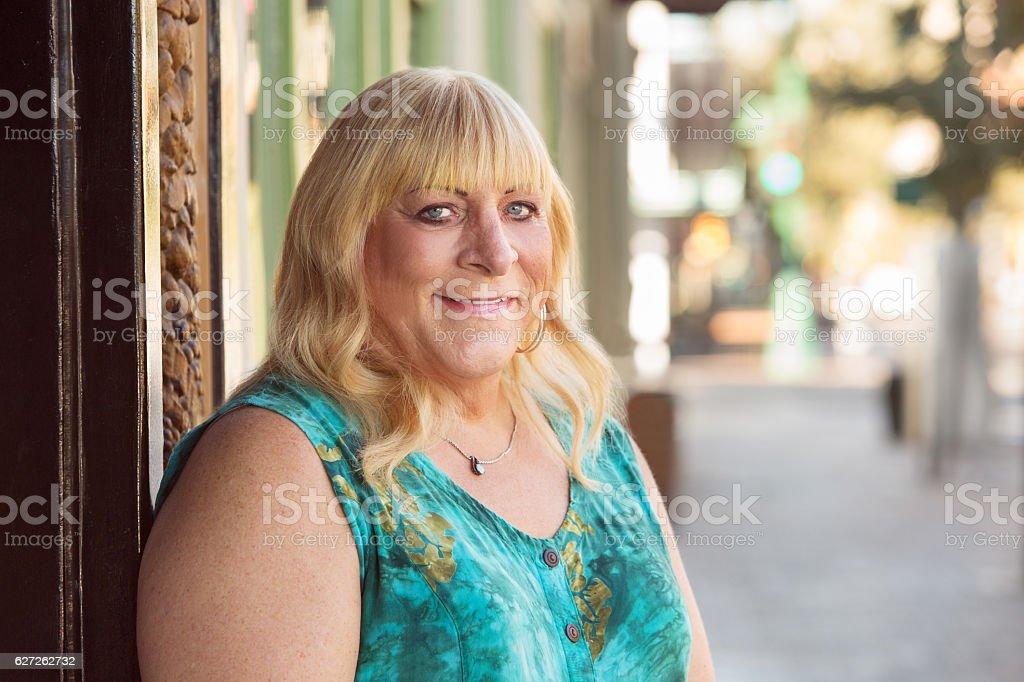 Transgender blond lady smiling outside stock photo