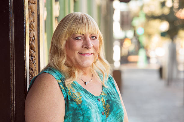 Transgender blond lady smiling outside Smiling blond middle aged transgender lady in blond hair and green top transgender stock pictures, royalty-free photos & images