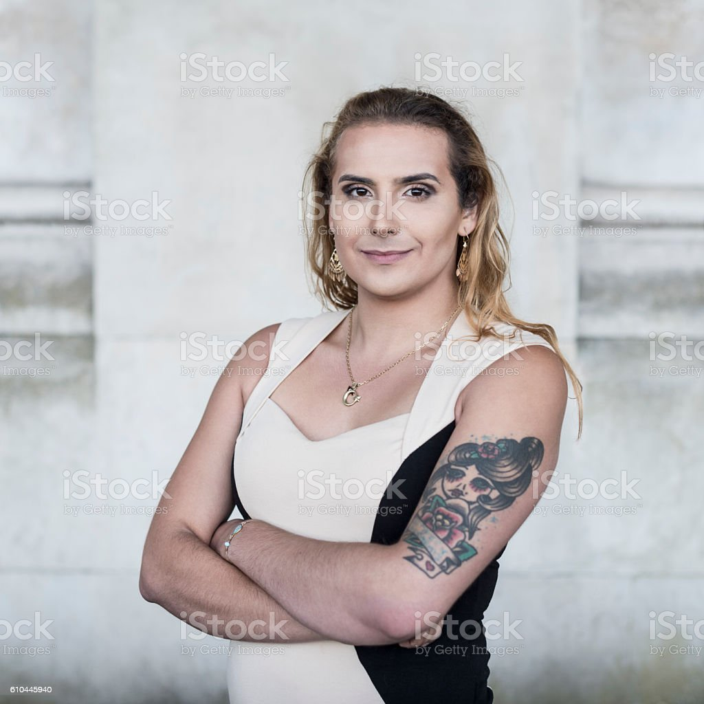 Transgender female with tattoo on arm looking towards camera stock photo