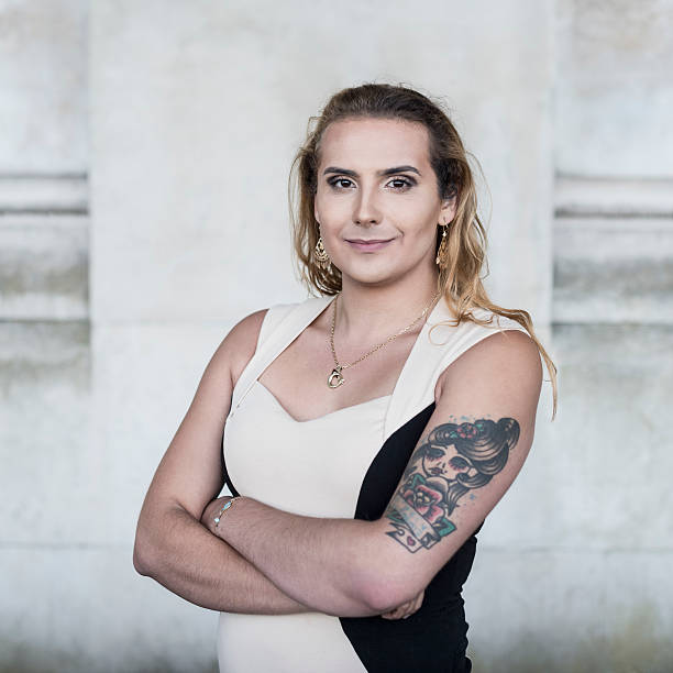 Transgender female with tattoo on arm looking towards camera Portrait of transgender female with arms folded looking at camera transgender stock pictures, royalty-free photos & images