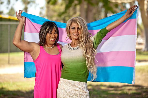 Transgender females holding Pride flag behind them stock photo