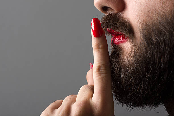 Transgender Making Silence Gesture Bearded Man with Red Lipstick on His Lips and Nail Polish Making Silence Gesture gay man stock pictures, royalty-free photos & images
