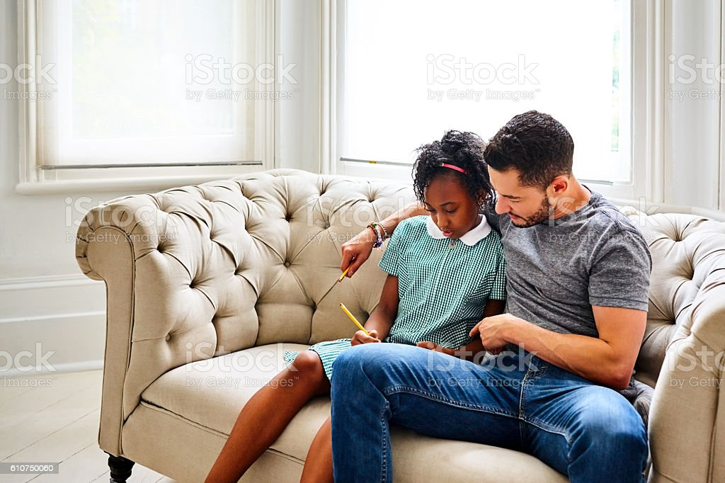Transgender male helping his daughter with homework stock photo