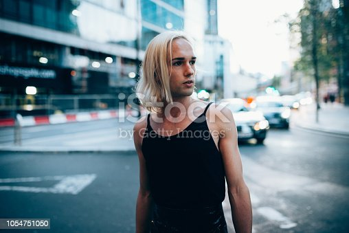 Portrait of transgender man in female clothing and with straight dyed blond hair.