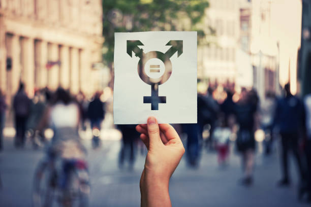 transgender symbol Hand holding a paper sheet with transgender symbol and equal sign inside. Equality between genders concept over a crowded city street background. Sex rights as a metaphor of social issue. transgender stock pictures, royalty-free photos & images