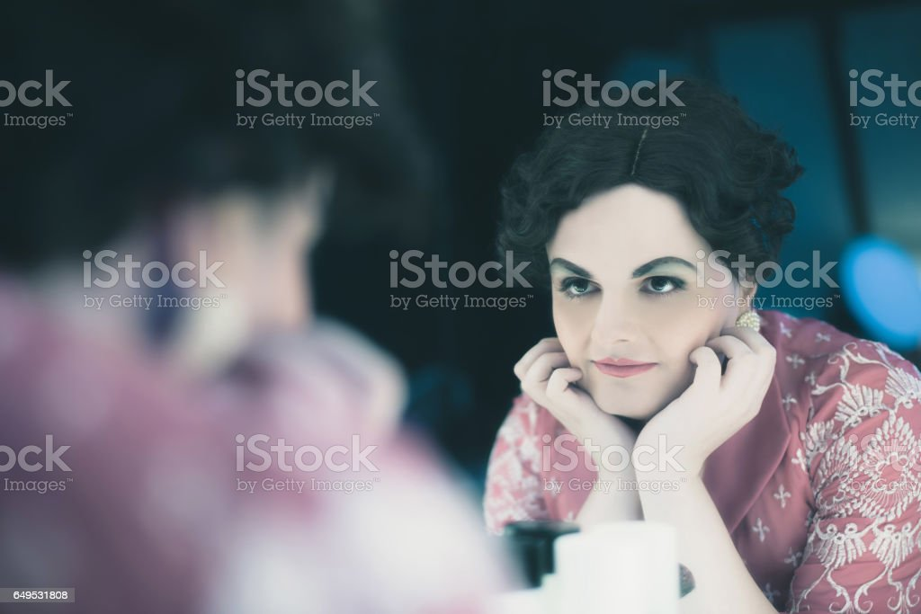 Transgender woman vintage 1920s fashion looking in mirror. stock photo