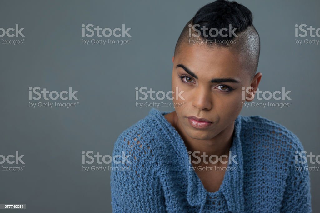 Transgender woman wearing blue sweater over gray background stock photo