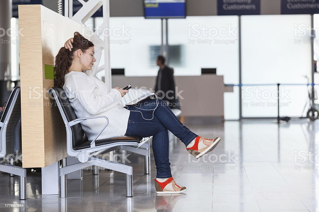 Transit passenger with devices waiting flight in airport lounge royalty-free stock photo