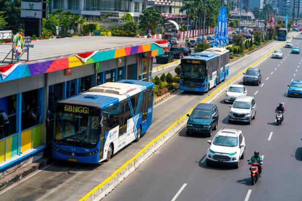 Transjakarta Bus Stop Station in Jakarta Street, Indonesia Jakarta, Indonesia - August 20, 2018: view showing Transjakarta bus stop shelter, cars and motorcycle on the other way of Jakarta street bus rapid transit stock pictures, royalty-free photos & images