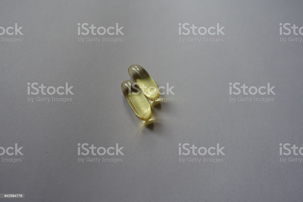 Translucent capsules of fish oil (two items) stock photo