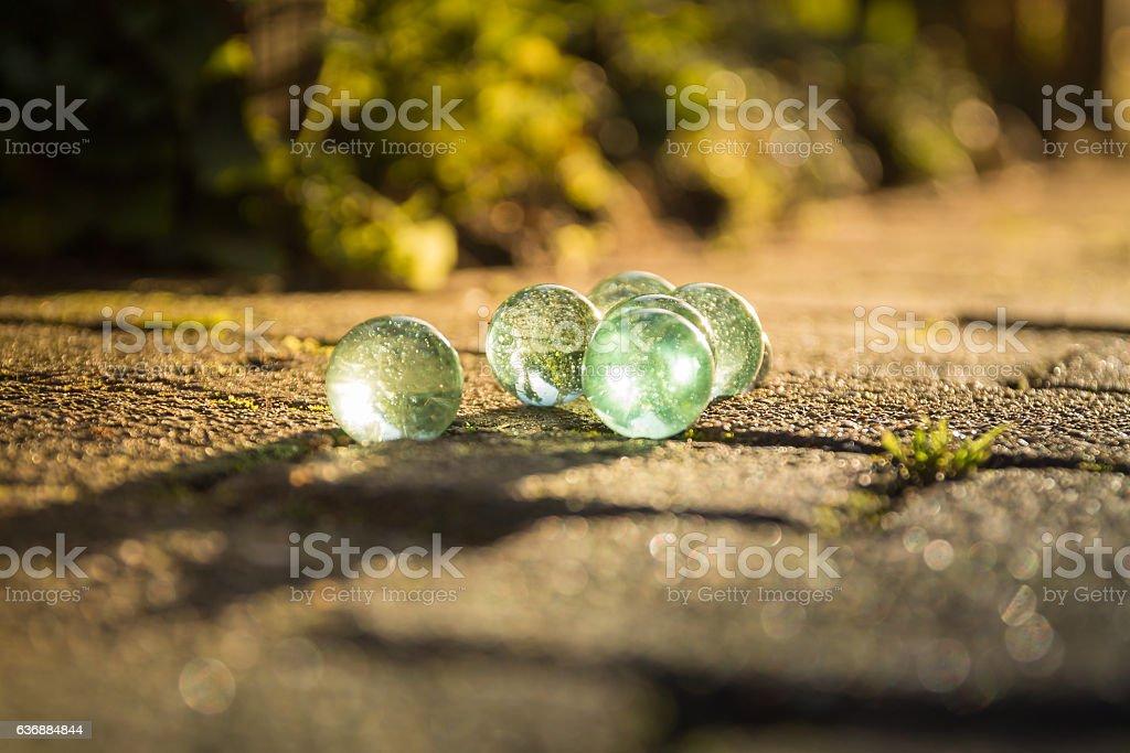 Translucent glass marbles on the sidewalk. – Foto