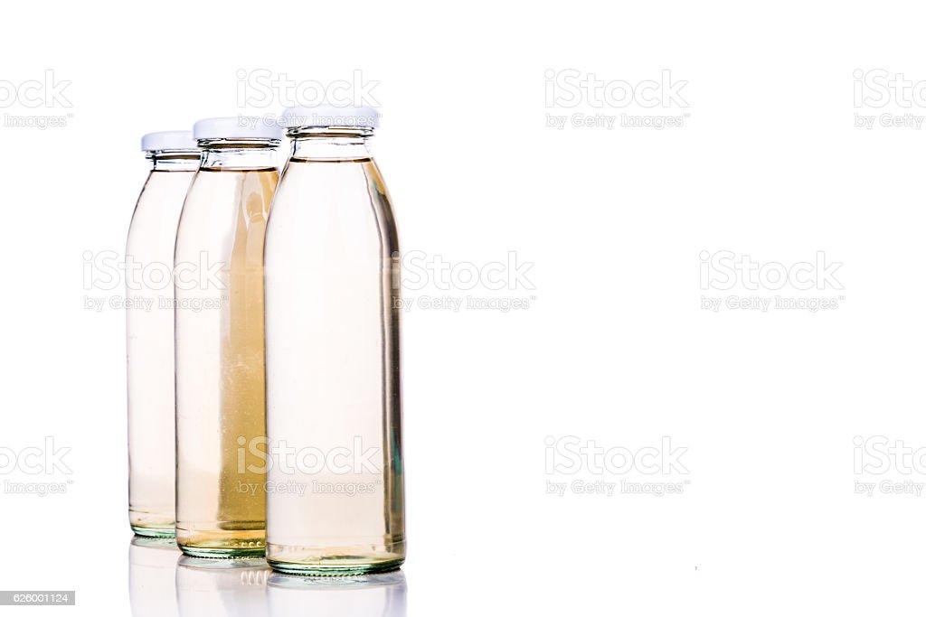 Translucent liquid in glass bottle on white background stock photo