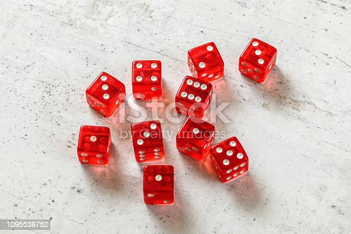 istock 10 translucent red dices on white concrete board. 1095536752