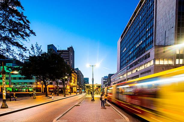 TransMilenio Bus System in Bogota, Colombia Bogota, Colombia - January 10, 2015: TransMilenio bus passing through a special, dedicated lane reserved for the bus system. People can be seen walking by the streets. bus rapid transit stock pictures, royalty-free photos & images