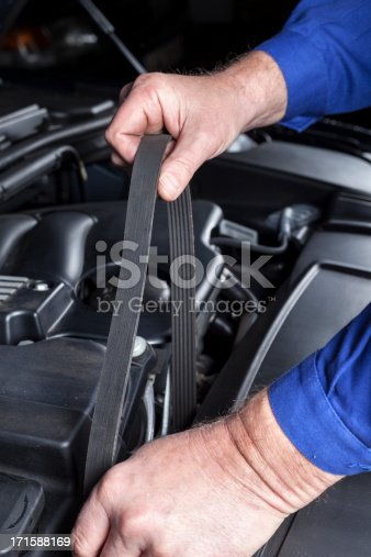 Mechanic is changing the transmission belt of a modern car engine.