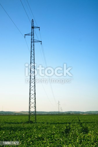 Transmission lines in the field over clear blue sky