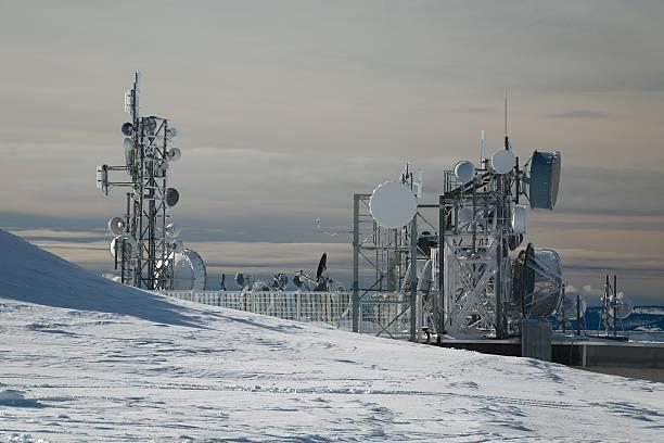 transmitter towers on a hill in winter - emissione radio televisiva foto e immagini stock