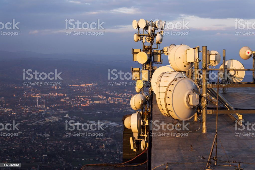Transmitters and aerials on telecommunication tower during sunset stock photo