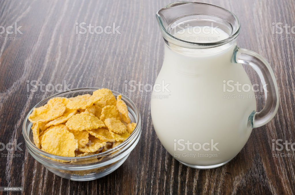 Transparent bowl with corn flakes and jug of milk stock photo