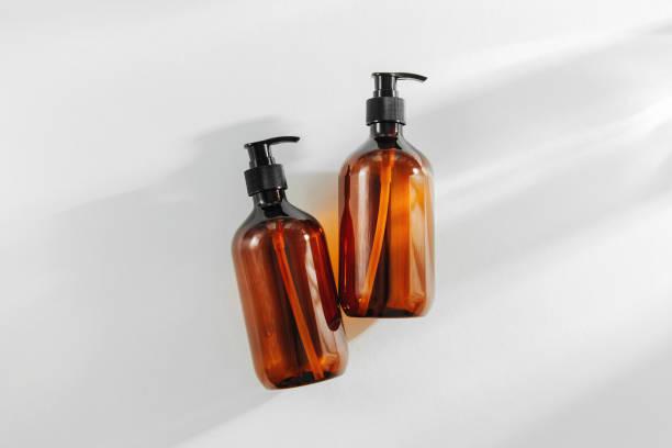 frascos marrons transparentes para o champô, o sabão ou o outro cosmético no fundo branco. - shampoo - fotografias e filmes do acervo