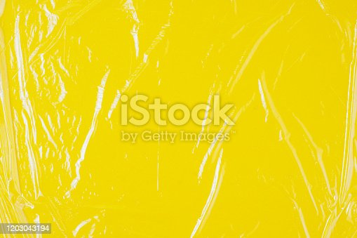 istock Transparent cellophane texture on an yellow backing 1203043194