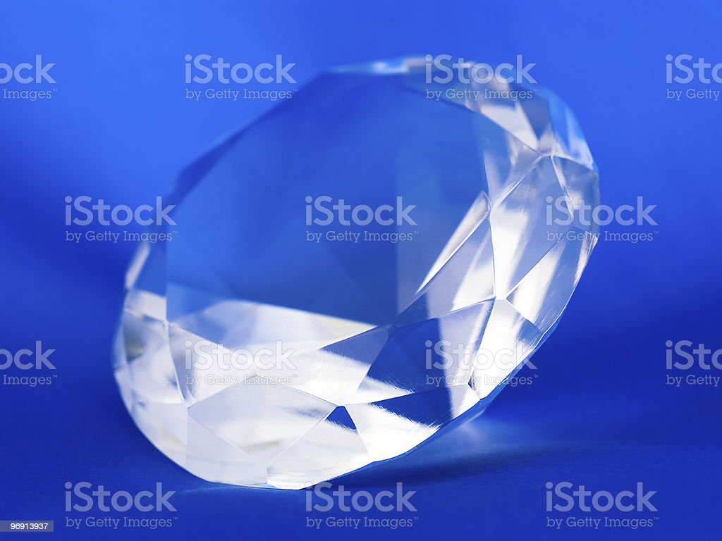 Transparent clear crystal gemstone on a blue background royalty-free stock photo