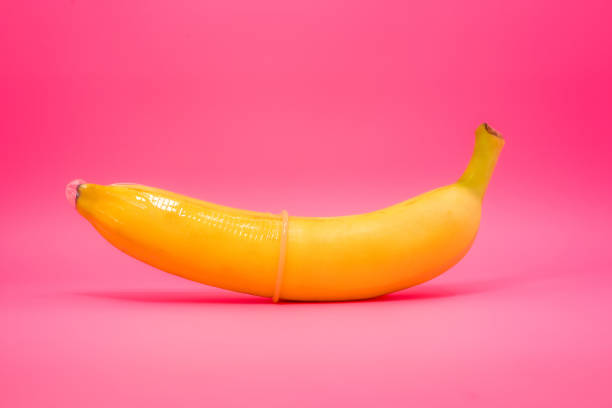 Transparent condom placed on banana. concept of sexual protection stock photo