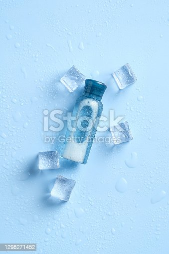 istock Transparent cosmetic bottle with ice cubes on blue background. Clear beauty product package, packaging branding mockup 1298271452