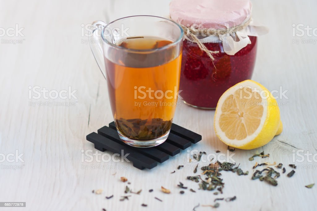 Transparent cup of tea, a jar of raspberry jam, a yellow cut lemon on a wooden stand on a light rustic table royalty-free stock photo