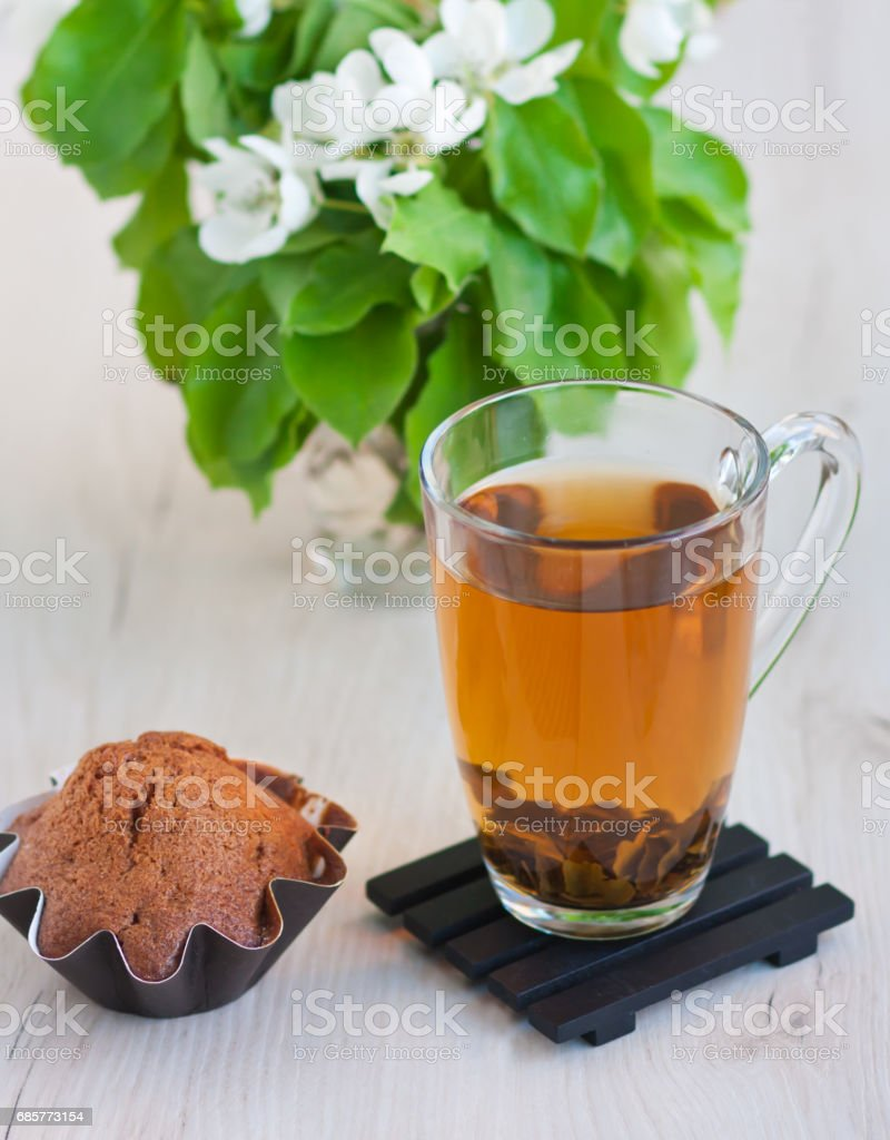 Transparent cup of tea, sprig of blossoming apple-tree, fresh cupcake on a wooden stand on a light rustic table royalty-free stock photo