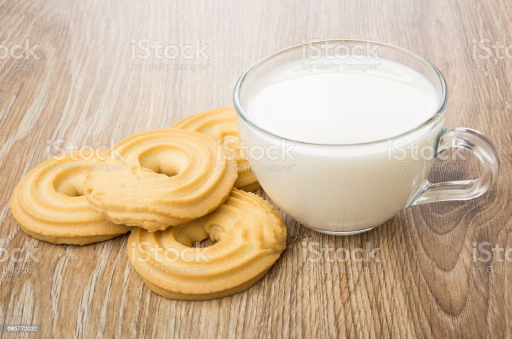 Transparent cup with milk and cookies in form ring royalty-free stock photo