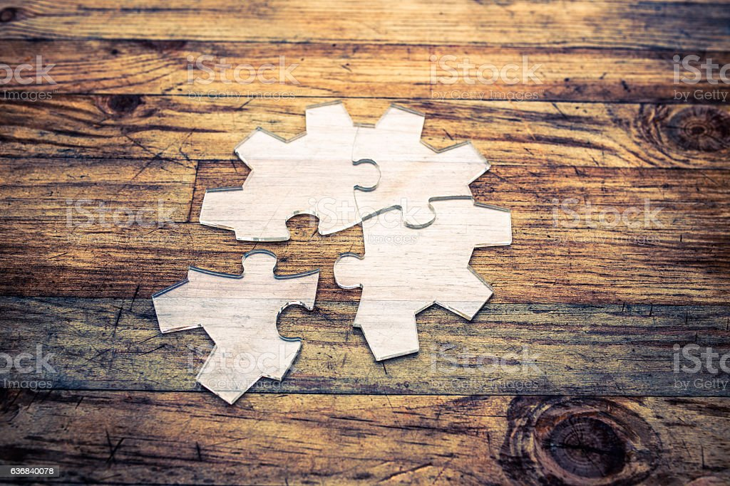 Transparent gear shape jigsaw puzzle on wood background stock photo