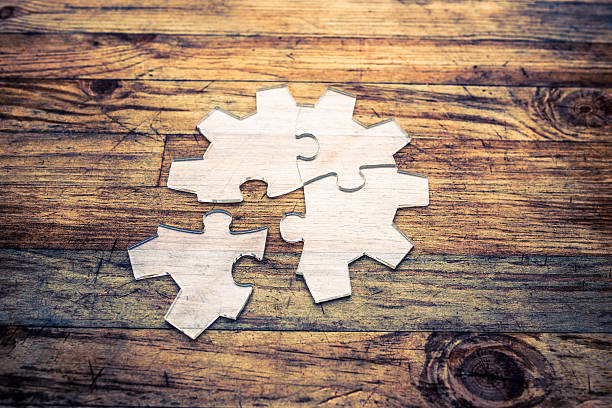Transparent gear shape jigsaw puzzle on wood background stock photo