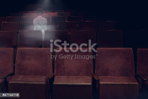 istock transparent ghost little girl appears between vintage seat in movie theater, horror film, halloween horror concept. 847144118