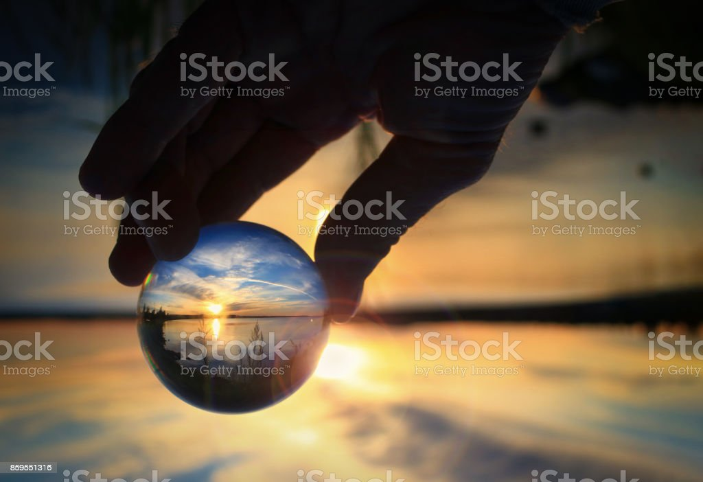 Transparent glass ball reflecting a sunset on the lake stock photo