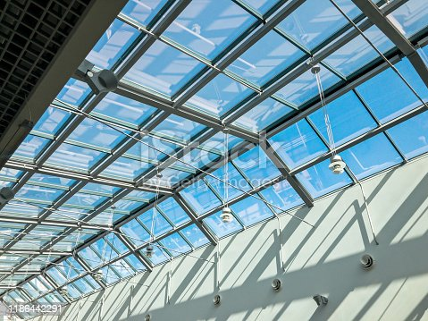 transparent glass ceiling of the modern building under bright blue sky