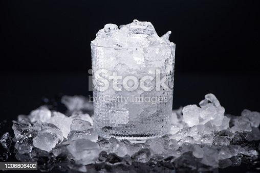transparent glass filled with smashed ice isolated on black