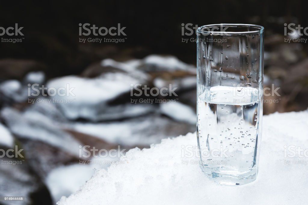 A transparent glass glass with drinking mountain water stands in the...
