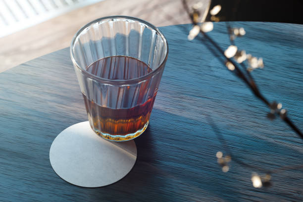 transparentes glas mit tee und bier-achterbahn auf holztisch. 3d rendering. - untersetzer stock-fotos und bilder