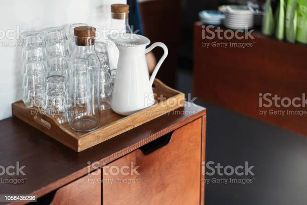 Transparent glasses and white metal jar on wooden cupboard in cafe picture id1058435296?b=1&k=6&m=1058435296&s=612x612&h=v2sbly1g16c7pulsbs73ihpikxidz0yw pvwvuueurm=