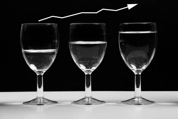 Transparent glasses with water growing business chart. stock photo