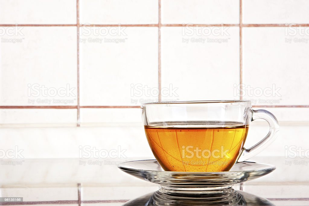 Transparent glassy tea cup on the tiled background royalty-free stock photo
