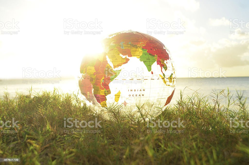 transparent globe on grass and bright sunbeam stock photo