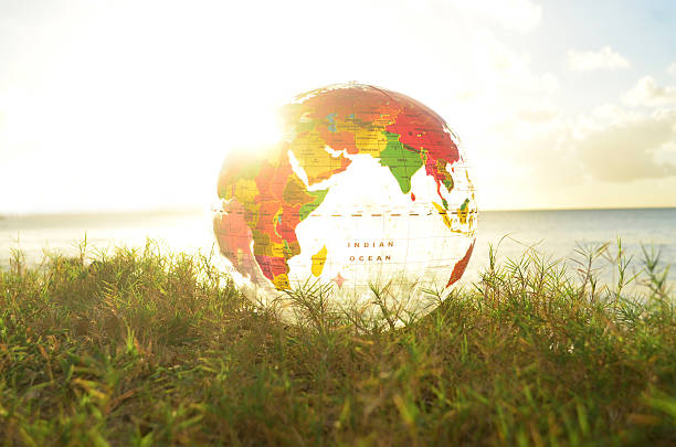 transparent globe on grass and bright sunbeam picture of brightly lit transparent globe showing Africa and Asia. Globe rests on grass against a beach backdrop with horizon. Horizon is aligned with the equator on the globe.  equator stock pictures, royalty-free photos & images