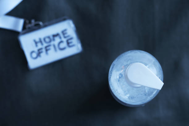 transparent hand sanitizer gel with a badge on a dark background - shifts call centre foto e immagini stock