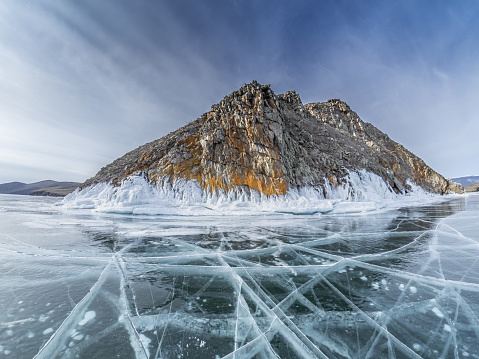 Transparent ice with cracks and rifts on Lake Baikal near frozen cliff with stones covered by snow and hoar frost.