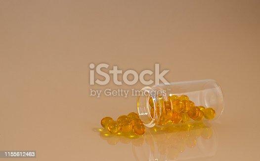 istock Transparent jar with yellow pills 1155612463