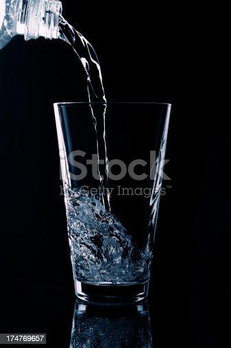 1169153675 istock photo Transparent liquid pouring into glass. 174769657